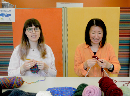 A member and staff knitting together